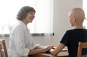 Smiling doctor support sick female cancer patient at meeting