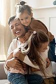 Playful little children embracing cuddling joyful father.