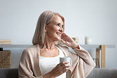 Happy dreamy middle aged woman holding cup of tea.