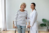 Elderly woman holding rollator feels satisfied after therapy with physiotherapist