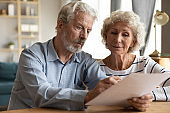 Mature couple read medical insurance terms seated at table indoors