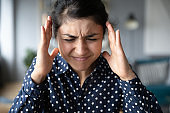 Indian woman suffering from strong head ache or loud noises.