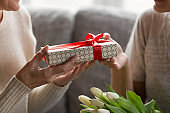 Close up image elderly womans hands holding present.