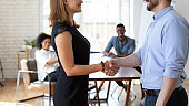 Diverse colleagues shake hands closing deal in office