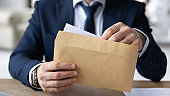 Close up young businessman opening envelope with paperwork correspondence.