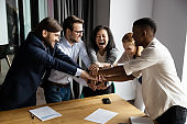 Cheerful diverse workmates stack palms arms together celebrating common success