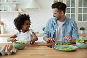 Happy multiracial family enjoying cooking healthy food.