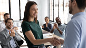 Male boss handshake female employee greeting with success at meeting