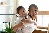Little adorable daughter piggybacks her young Asian mother