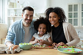 Portrait of happy mixed race family cooking in kitchen.
