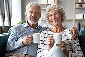 Smiling retired family spouses enjoying lazy weekend morning time.