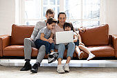 Happy family with two children having good time using laptop.