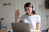 Smiling pretty young caucasian woman greeting colleagues at online video call.