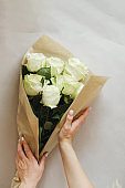 woman florist making bouquet of white flowers indoor. Female florist preparing bouquet of roses at flower shop. entrepreneurship, small business, workplace concept