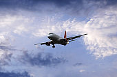 Airplane flying under beautiful evening clouds, front view
