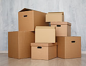 moving day or postal delivery concept - brown cardboard boxes stacked on the floor over gray wall