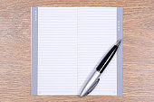 empty contact notebook and pen on wooden table