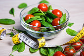diet and weight loss concept - salad with spinach and tomatoes and measure tape on wooden table