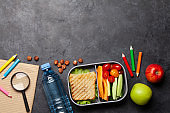 School lunch box and education stationery on stone table