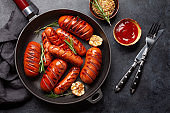 Hot grilled sausages in a frying pan