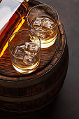 Scotch whiskey bottle, glass and old barrel