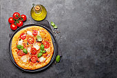 Tasty homemade pizza with tomatoes and basil
