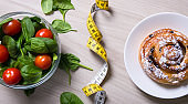 healthy and unhealthy food - salad with spinach and tomatoes, measure tape and sweet bun