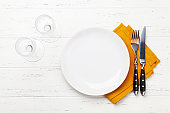 White empty plate, fork, knife and napkin