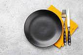 Black empty plate, fork, knife and napkin