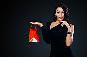 Black friday sale concept for shop. Shopping girl holding red bag isolated on dark background. Woman pointing to looking left on copy space.