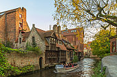 Tourists riding the tourboat in a canal to see the historical buildings and natural beauty at the Dijver canal of Brugge, Belgium.