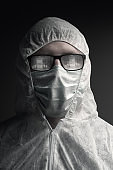 portrait of physician with protective suit and steamed up glasses which reflecting an empty corridor of hospital