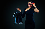 Black Friday sale concept for shop. Girl in sunglasses holding big bag isolated on dark background at shopping. Woman pointing to looking on copy space for sales text.