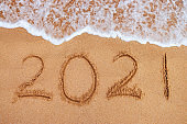 Happy New Year 2021 concept, lettering on the beach. Written text on the sea beach at sunrise