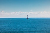 Sea and sailing wind boat. Sailboat over blue waves and sunny sky