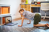 Little boy exercising at home with laptop during quarantine