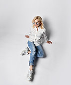 Top view of young cheerful blond woman in casual clothing, white sneakers and sunglasses sitting on floor and smiling