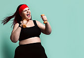 Fitness spring diet weight loss concept. Screaming loud plus-size overweight woman does exercises with weights dumbbell