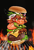 Big hamburger roasted on barbecue BBQ grill with bright flaming fire against black background. Beef cutlet, ham, cheese, vegetables and greens