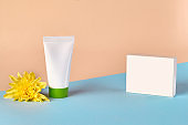 White cosmetic tube with green cap and no label next to yellow chrysanthemum flower and box against colorful studio background. Close up, copy space