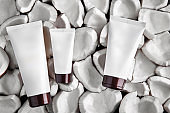 Three white different sized tubes with no logo or label on pieces or parts of coconut background. Cosmetic packaging, containers. Close up, copy space