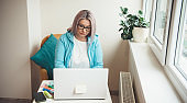 Front view photo of a busy caucasian senior lady with blonde hair working at the laptop from home near the window