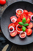 tomato salad delicious vegetables snack bush green stems and petals Menu concept serving size. food background top view copy space for text keto or paleo diet