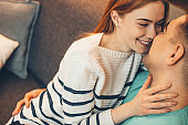 Charming caucasian lady with red hair and freckles is touching her lover's face while sitting on the sofa