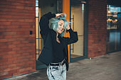 Delightful caucasian woman with blue hair posing outside while moving and dancing