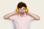 Amazed caucasian ginger boy wearing headphones listening to music on a white studio wall