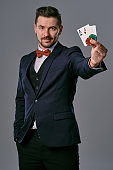 Man in black classic suit and red bow-tie showing two playing cards and chips, posing on gray studio background. Gambling, poker, casino. Close-up