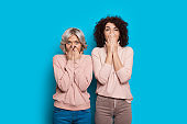 Two lovely caucasian sisters with curly hair are covering their mouths while posing on a blue background