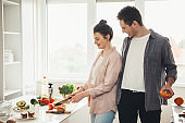 Young caucasian couple preparing food together in the kitchen slicing fruits and vegetables