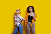 Cheerful caucasian sisters with nice curly hair are listening to music using headphones while posing on a yellow background